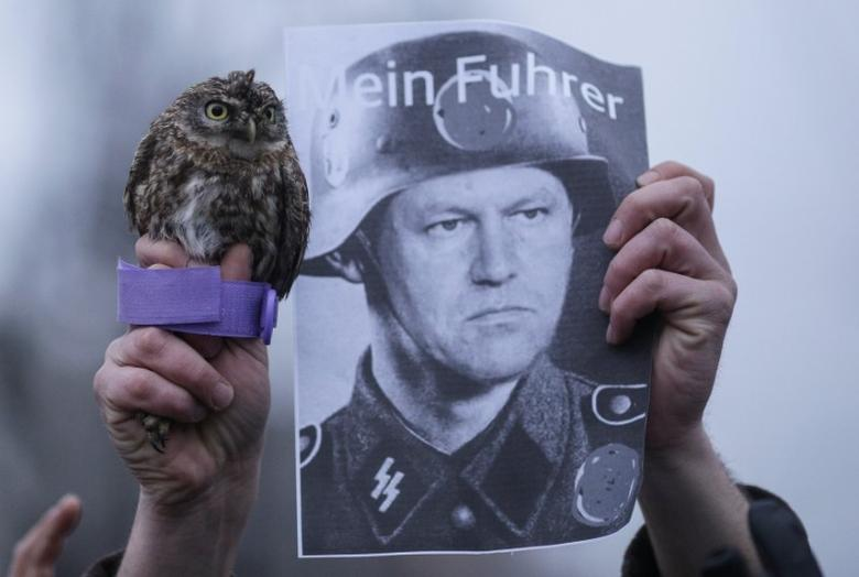 A pro-government protester holds up a baby owl and an image of Romanian President Klaus Iohannis depicted as a Nazi soldier of Hitler's paramilitary SS Schutzstaffel organisation in front of the presidential office in Bucharest, Romania February 6, 2017. Inquam Photos/Octav Ganea via REUTERS