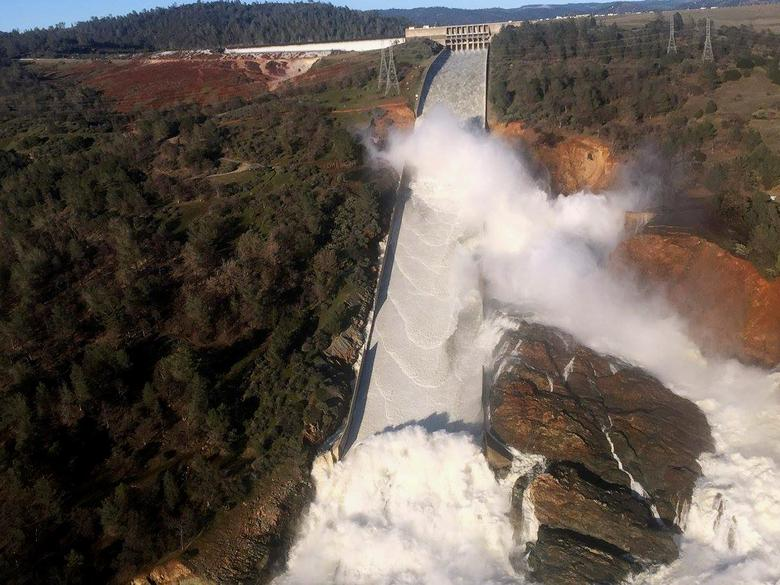 A damaged spillway with eroded hillside is seen in an aerial photo taken over the Oroville Dam in Oroville, California, U.S. February 11, 2017.  California Department of Water Resources/William Croyle/Handout via REUTERS