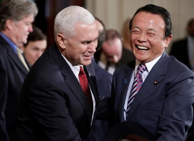 2月15日、麻生太郎副総理は衆院財務金融委員で、春にも予定されているペンス米副大統領の訪日時に開催される日米経済対話の初回では「米側がスタッフ不足」として、「詰めた話が出る感じはしない」と述べた。写真は10日、安倍・トランプ日米両首脳の共同会見前に談笑する麻生副総理(右)とペンス米副大統領(左)。ワシントン・ホワイトハウスで撮影(2017年 ロイター/Joshua Roberts)