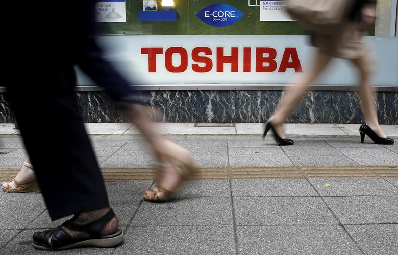 FILE PHOTO -  Pedestrians walk past a logo of Toshiba Corp outside an electronics retailer in Tokyo September 14, 2015.   REUTERS/Toru Hanai/File Photo