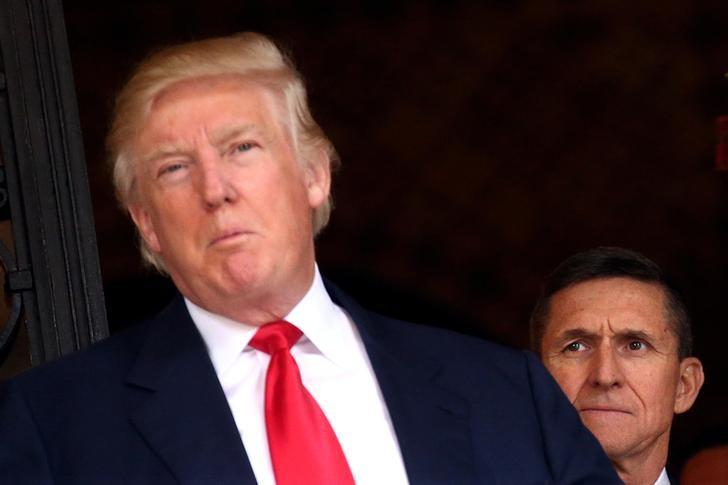 U.S. Army Lieutenant General Michael Flynn looks at U.S. President-elect Donald Trump as he talks with the media at Mar-a-Lago estate where Trump attends meetings, in Palm Beach, Florida, U.S., December 21, 2016. REUTERS/Carlos Barria/File Photo
