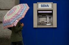 El Grupo BBVA ha vendido en el mercado un 1,7 por ciento de su participación en el banco chino China Citic Bank Corporation Limited (CNCB) por unos 554 millones de euros, generando una plusvalía neta de aproximadamente 177 millones de euros. En la imagen, una mujer con un paraguas ante un cajero de BBVA en Madrid en abril de 2016. REUTERS/Andrea Comas/File Photo