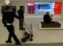 Passersby watch the performance of stocks on a financial news television screen in the business district of Toronto, Canada, January 30, 2017. REUTERS/Chris Helgren