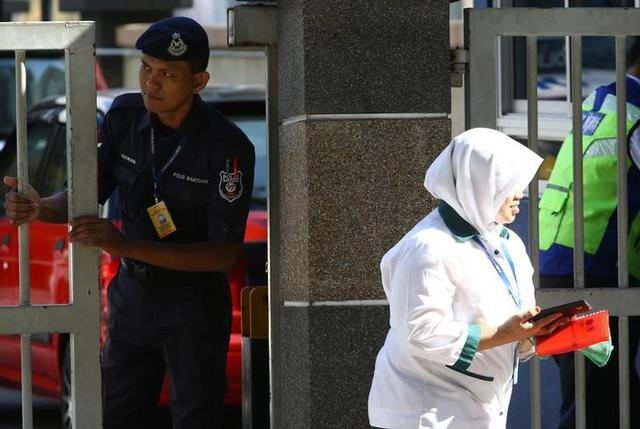 A police officer looks on as a hospital staff walks past outside the morgue at Kuala Lumpur General Hospital where Kim Jong Nam's body is held for autopsy in Malaysia, February 17, 2017. REUTERS/Athit Perawongmetha