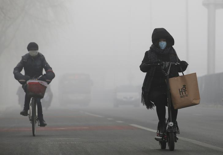 People ride amid the smog in Beijing, China, February 14, 2017. REUTERS/Jason Lee