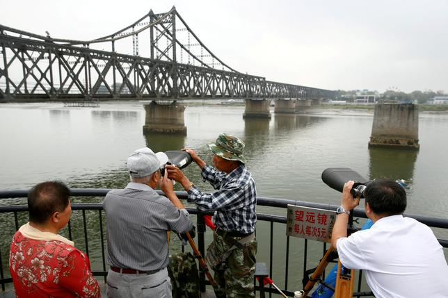 FILE PHOTO: People look through binoculars towards North Korea from the destroyed bridge across Yalu River that once linked North Korea's Sinuiju and Dandong, China's Liaoning province, September 10, 2016.  REUTERS/Thomas Peter/File Photo