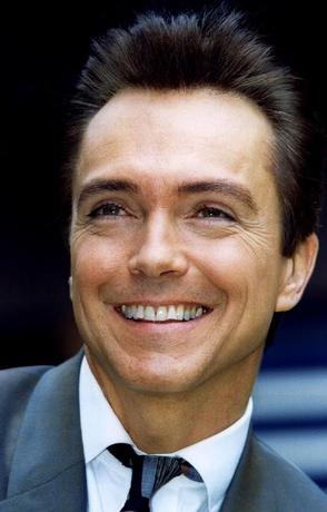 David Cassidy smiles for photographers outside the Phoenix theatre in London, Britain, October 23, 1995. REUTERS/Andrew Shaw/File Photo