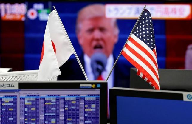 4月20日、生半可な考えは、まったくのでたらめよりも危険な場合がある。トランプ米大統領の為替レートに関する考えはその良い例だ。写真は1月、都内の外為ディーリングルームの画面に映ったトランプ大統領のニュース映像と日米国旗(2017年 ロイター/Toru Hanai)