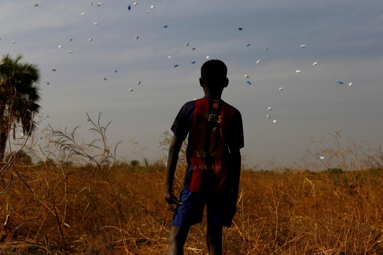 A boy watches sacks of food drop to the ground during a United Nations World Food Programme (WFP) airdrop close to Rubkuai village in Unity State, northern South Sudan, February 18, 2017. REUTERS/Siegfried Modola/File Photo