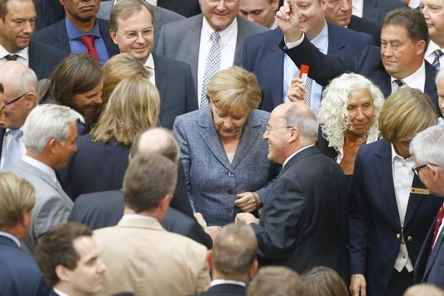 FILE PHOTO - German Chancellor Angela Merkel and members of the lower house of parliament cast their votes on Greece's third bailout programme, during a session of the Bundestag, in Berlin, Germany, August 19, 2015. REUTERS/Axel Schmidt