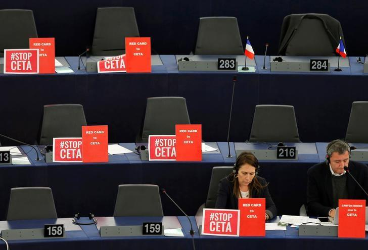 Posters reading ''stop CETA'' and ''red card to CETA'' are seen on MEPs' desks ahead of a voting session on the Comprehensive Economic Trade Agreement (CETA) between the EU and Canada, in Strasbourg, France, February 15, 2017.  REUTERS/Vincent Kessler