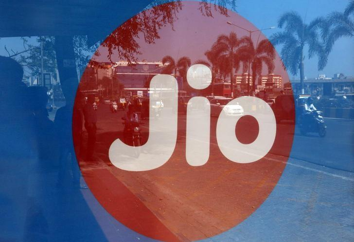 Commuters are reflected on an advertisement of Reliance Industries' Jio telecoms unit, at a bus stop in Mumbai, India, February 21, 2017. REUTERS/Shailesh Andrade