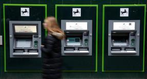 Una mujer camina frente a cajeros automáticos del Banco Lloyds, en Manchester, Gran Bretaña. 21 de febrero 2017.    Lloyds Banking Group reportó el miércoles su ganancia más alta para todo un año en una década, en momentos en que el banco respaldado por los contribuyentes se acerca a una recuperación completa de su pasado sumido en la crisis.REUTERS/Phil Noble