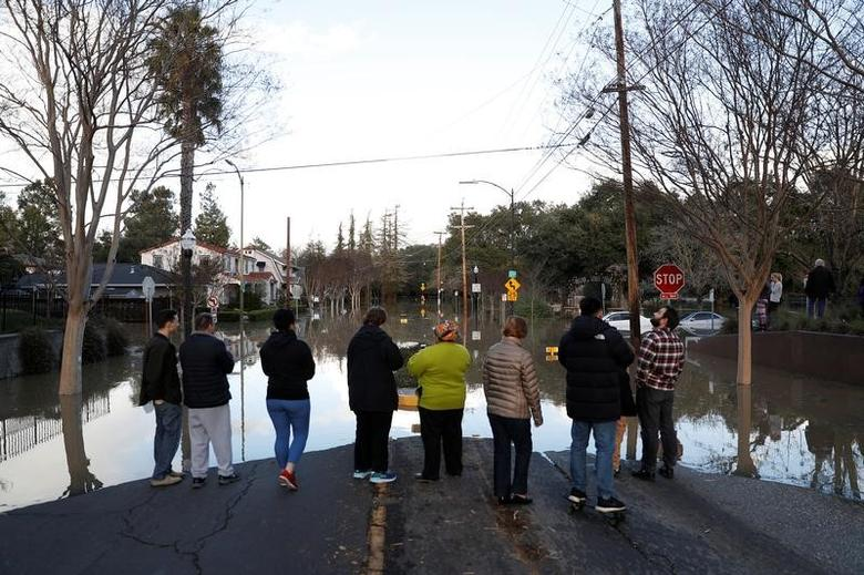 People stand by a flooded street near William Street Park after heavy rains overflowed nearby Coyote Creek in San Jose, California, U.S., February 21, 2017. REUTERS/Stephen Lam
