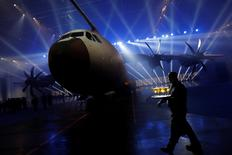 A waiter walks past an Airbus A400M military transport plane is parked at the Airbus assembly plant during an event in the Andalusian capital of Seville, southern Spain, December 1, 2016. REUTERS/Marcelo del Pozo