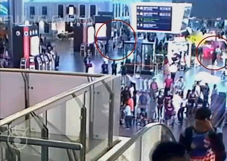 A still image from a CCTV footage appears to show a woman in a white shirt (circled in red on right) walking away after accosting a man purported to be Kim Jong Nam (circled in red on left) at Kuala Lumpur International Airport in Malaysia on February 13, 2017. FUJITV/ via Reuters TV