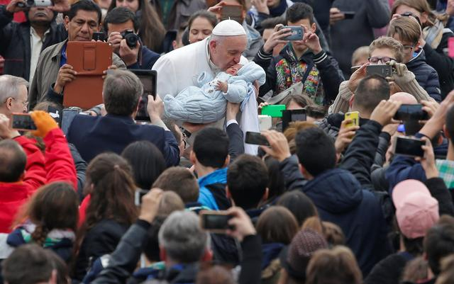 Pope Francis kisses a baby as he leads the weekly general audience in Saint Peter's Square at the Vatican February 22, 2017. REUTERS/Max Rossi