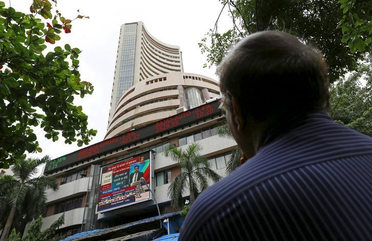 A man looks at a screen across a road displaying the Sensex on the facade of the Bombay Stock Exchange (BSE) building in Mumbai, India, June 29, 2015.  REUTERS/Danish Siddiqui/Files