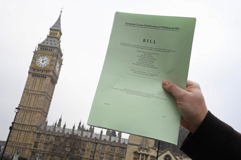 A journalist poses with a copy of the Brexit Article 50  bill, introduced by the government to seek parliamentary approval to start the process of leaving the European Union, in front of the Houses of Parliament in London, Britain, January 26, 2017. REUTERS/Toby Melville