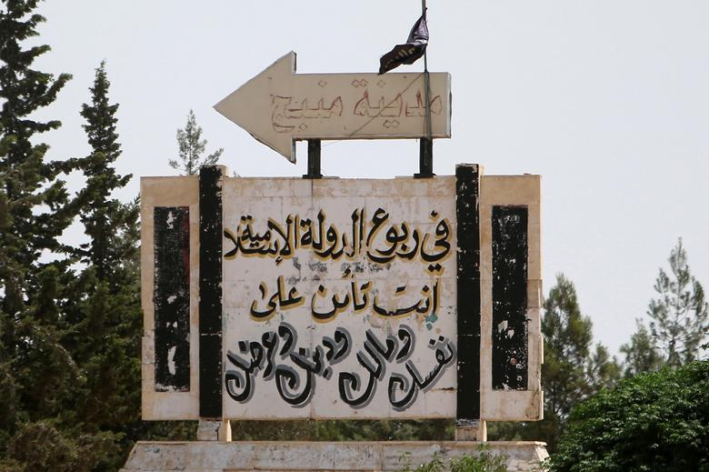 FILE PHOTO: A road sign shows the direction to Manbij city, as seen from the western entrance of the city, in Aleppo Governorate, Syria June 19, 2016. The Arabic words read 'Under the Islamic State rule, you insure your self, money, religion and honour'. REUTERS/Rodi Said/File Photo