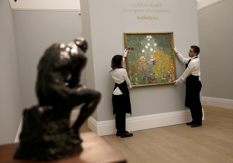 Workers pose with Gustav Klimt's ''Bauerngarten (Blumengarten)'' ahead of an upcoming sale at Sotheby's auction house, in London, Britain February 22, 2017.   REUTERS/Peter Nicholls/Files
