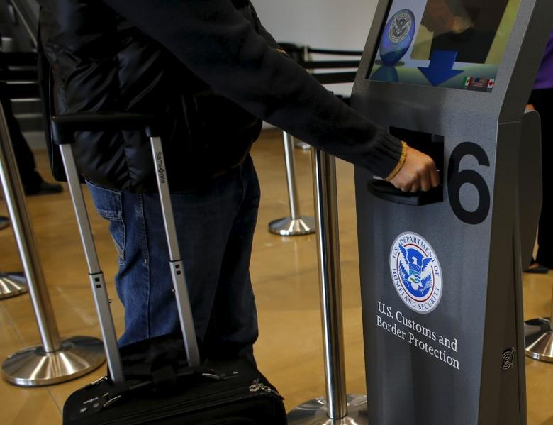 A traveler has his passport scanned as he passes through U.S. Customs and Immigration after using the Cross Border Xpress pedestrian bridge between San Diego and the Tijuana airport on the facility's opening day in Otay Mesa, California December 9, 2015. REUTERS/Mike Blake