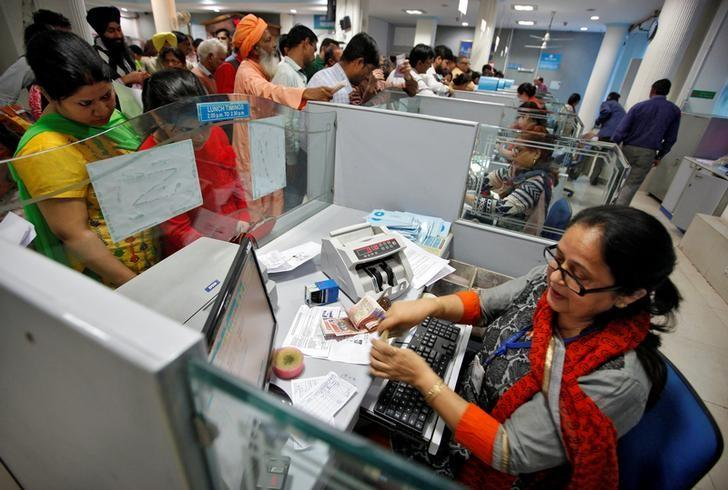 A cashier counts Indian banknotes as customers wait in queues inside a bank in Chandigarh, India, November 10, 2016. REUTERS/Ajay Verma/File Photo