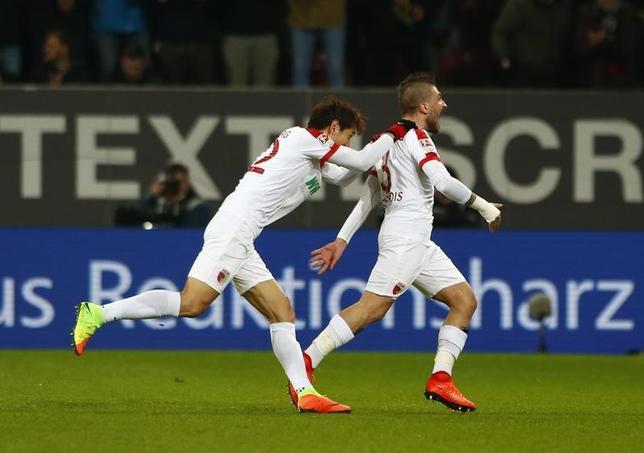 3月3日、サッカーのドイツ1部ブンデスリーガ、宇佐美貴史が所属するアウクスブルクはライプチヒと2─2で引き分けた。写真は得点を喜ぶアウクスブルクの選手たち(2017年 ロイター/Michaela Rehle)