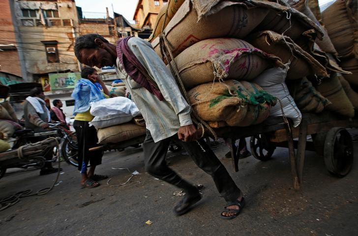 A labourer pulls a cart loaded with sacks of spices at a wholesale spice and chemical market in the old quarters of Delhi, India, December 19, 2016.  REUTERS/Adnan Abidi/Files