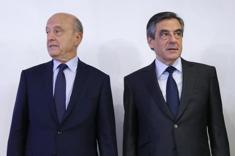 Francois Fillon (R), former French prime minister, and Alain Juppe, current mayor of Bordeaux, stand together after the results in the second round for the French center-right presidential primary election in Paris, France, November 27, 2016. REUTERS/Gonzalo Fuentes/Files