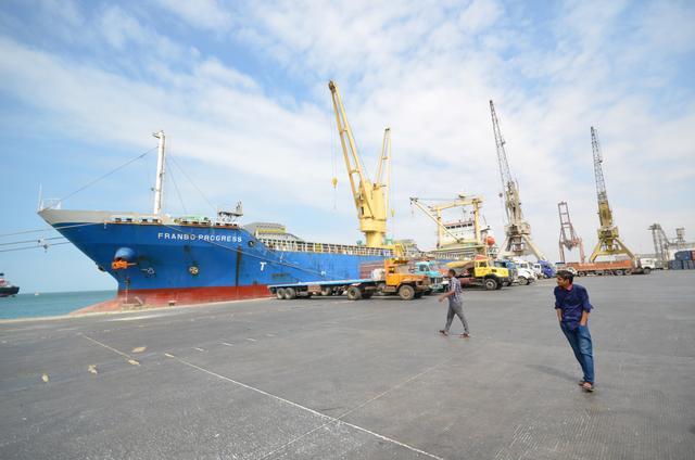 FILE PHOTO - People walk past a ship docked at the Red Sea port of Hodeidah, Yemen February 1, 2017. REUTERS/Abduljabbar Zeyad/Files