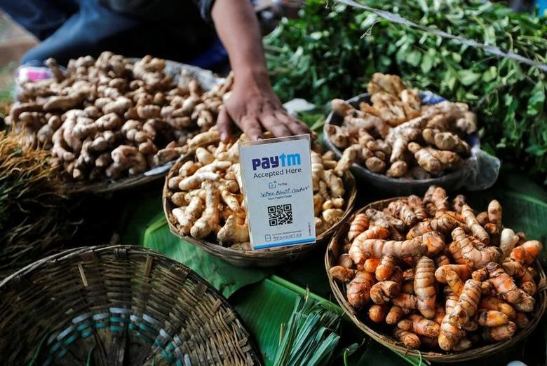An advertisement board displaying a QR code for Paytm, a digital wallet company, is seen placed amidst vegetables at a roadside vendor's stall in Mumbai, India, November 19, 2016. Picture taken November 19, 2016. REUTERS/Shailesh Andrade/File Photo