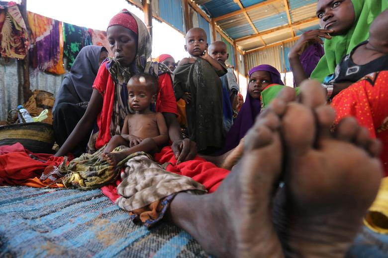 An internally displaced Somali woman sits with her children inside their general shelter at the Al-cadaala camp in Mogadishu. REUTERS/Feisal Omar