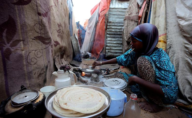 An internally displaced Somali woman prepares traditional pancakes outside their family makeshift shelter at the Al-cadaala camp in Mogadishu. REUTERS/Feisal Omar