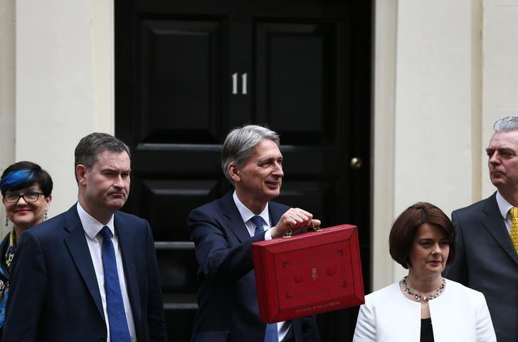 Britain's Chancellor of the Exchequer Philip Hammond stands outside 11 Downing Street with his Treasury team before delivering his budget to the House of Commons in London, Britain March 8, 2017.    REUTERS/Neil Hall