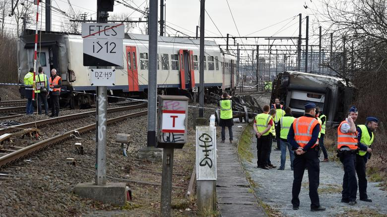 Rescuers and police officers stand next to the wreckage of a passenger train after it derailed in Kessel-Lo near Leuven, Belgium February 18, 2017. REUTERS/Eric Vidal