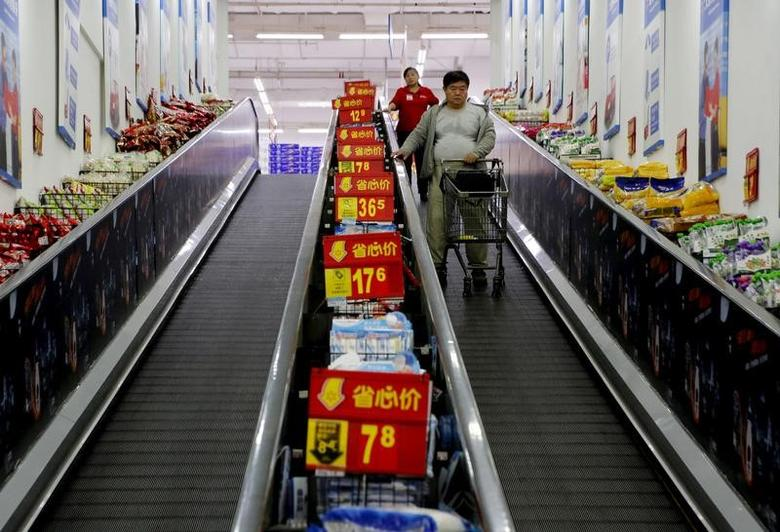 Shoppers ride on a travelator at a supermarket in Beijing, China, October 15, 2015.   REUTERS/Kim Kyung-Hoon/File Photo
