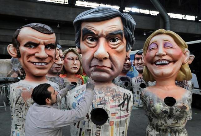 3月6日、政治腐敗はフランスでは珍しくない。そして、政治というゲームの勝者、あるいはそれに近い立場にある政治家であれば、法的な処罰を受けないことも日常茶飯事だ。だが、2017年の仏大統領選挙は政界が変わる契機となるかもしれない。写真は大統領選に名乗りを上げているフランソワ・フィヨン元首相(中央)、極右政党「国民戦線」のマリーヌ・ルペン党首(右)、元経済相のエマニュエル・マクロン氏の人形を製作する男性。ニースで2月撮影(2017年 ロイター/Eric Gaillard)