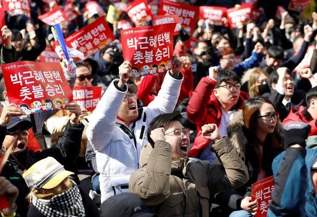 3月10日、韓国憲法裁は10日、朴槿恵大統領の罷免を決定した。写真は罷免決定を喜ぶ国民。ソウルで撮影(2017年 ロイター/Kim Hong-Ji)