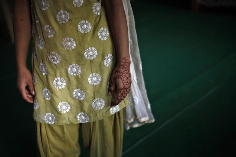 A girl with her hand decorated with henna stands inside a protection home on the outskirts of New Delhi November 9, 2012. REUTERS/Mansi Thapliyal/Files