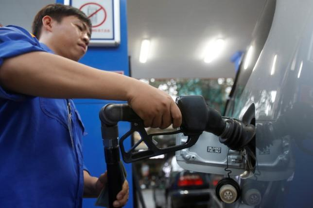 An employee pumps petrol into a car at a petrol station in Hanoi, Vietnam December 20, 2106. REUTERS/Kham