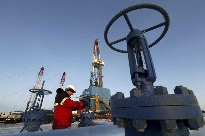 A worker checks a valve of an oil pipe at the Lukoil company owned Imilorskoye oil field outside the West Siberian city of Kogalym, Russia, in this January 25, 2016 file photo.   REUTERS/Sergei Karpukhin/File Photo