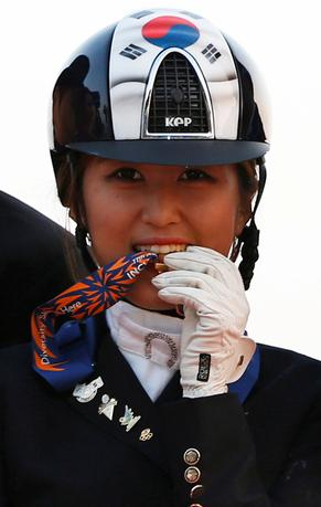 FILE PHOTO: South Korea's Chung Yoo-ra, then known as Chung Yoo-yeon, bites her gold medal as she poses after winning the equestrian Dressage Team competition at the Dream Park Equestrian Venue during the 17th Asian Games in Incheon September 20, 2014. REUTERS/Kim Hong-Ji/File Photo