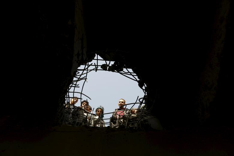 People look through a hole caused by a Saudi-led air strike on a bridge in Yemen's capital Sanaa March 23, 2016.REUTERS/Khaled Abdullah