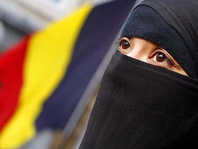 3月14日、欧州連合(EU)の欧州司法裁判所は、企業が職場でイスラム教徒のスカーフなどの宗教的な服装を禁じることは条件付きで認められるとの判断を示した。写真はベルギー・ブリュッセルに住む、フランス国籍の女性。同女性はイスラム教に改宗し、スカーフを被ることを選択していた。2010年4月撮影(2017年 ロイター/Yves Herman)