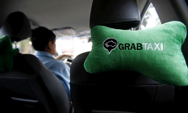 A GrabTaxi logo is seen on a car neck pillow in a taxi in Hanoi, Vietnam September 9, 2015.  REUTERS/Kham/File Photo