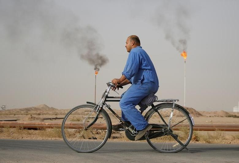 A worker rides a bicycle at Najaf oil refinery in Najaf, 160 km (99 miles) south of Baghdad, October 3, 2013.   REUTERS/Ahmad Mousa