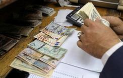 Человек пересчитывает доллары и евро в пункте обмена валют. Банки Евросоюза могут столкнуться с увеличением рисков, связанных с плохими кредитами объемом 1 триллион евро ($1,1 триллиона) после того, как Европейский центробанк сократит меры стимулирования, свидетельствуют внутренние документы ЕС, оказавшиеся в распоряжении Рейтер. REUTERS/Mohamed Abd El Ghany