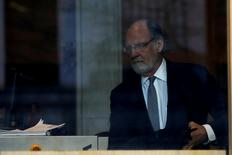 FILE PHOTO - Jon Corzine, former CEO of MF Global Holdings and former U.S. Senator and New Jersey Governor, is seen through a window as he arrives at the Manhattan federal court house in New York City, U.S. on March 9, 2017. REUTERS/Brendan McDermid/File Photo