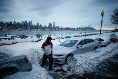 ساكن يمر بجوار سيارة عالقة بين الثلوج في نيوجيرزي يوم الثلاثاء. تصوير. إدواردو مونوز - رويترز